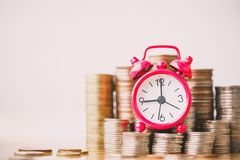 Red alarm clock on stack of coins in concept of savings and money growing or energy save. stock photography