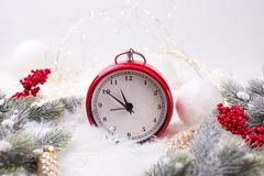 Red alarm clock - symbol of New Year, fir tree branches, berri stock photo
