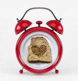 Red alarm clock with toast bread heart concept isolated on white background Stock Photo