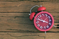 Red alarm clock vintage tone on old wooden background. Royalty Free Stock Photos