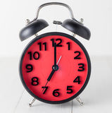 Red Alarm Clock on white table setting up at 7 Stock Images