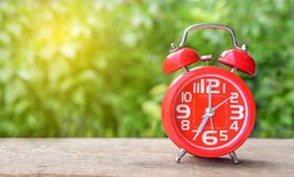Red alarm clock on wood table and green background with morning sun bright. space for text Stock Photo