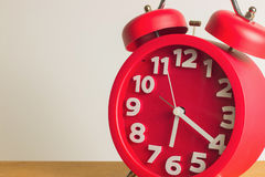 Red alarm clock on wooden. Red alarm clock close up on wooden table. Emphasizing copy space on left side Royalty Free Stock Photos