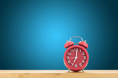 Red alarm clock on a wooden table on blue wall background.  stock image