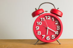 Red alarm clock on wooden. Red alarm clock on wooden table. Emphasizing copy space on left side Royalty Free Stock Photos