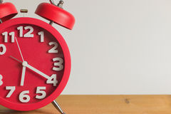 Red alarm clock on wooden. Red alarm clock on wooden table. Emphasizing copy space on left side Stock Photo