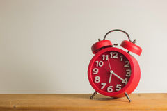 Red alarm clock on wooden. Red alarm clock on wooden table. Emphasizing copy space on left side for write text Royalty Free Stock Photos