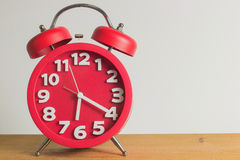 Red alarm clock on wooden. Red alarm clock on wooden table. Emphasizing copy space on right side Stock Photo