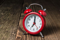 Red alarm clock on the wooden table. Red alarm clock at seven oclock on the wooden table Stock Image
