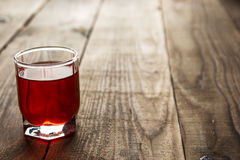 Red alcohol shot drink. On wooden background stock photo
