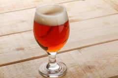 Red ale on light wood Royalty Free Stock Photos