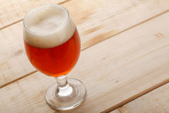 Red ale on light wood Royalty Free Stock Images