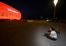 Red Allianz Arena. Two sports fans, a mother and son, admiring famous football arena at night. Allianz Arena, Munich, Germany royalty free stock photo