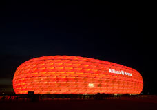Red Allianz Arena. Famous landmark, exterior of the Allianz Arena in Munich, Germany. Night shot, the arena lit with red light, night sky as space for text royalty free stock images