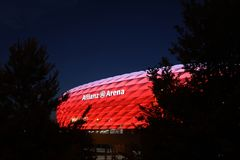 Red Allianz Arena. Famous landmark, exterior of the Allianz Arena in Munich, Germany. Night shot, the arena lit with red light, night sky as space for text, copy stock images