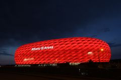 Red Allianz Arena. Famous landmark, exterior of the Allianz Arena in Munich, Germany. Night shot, the arena lit with red light, night sky as space for text, copy stock photo