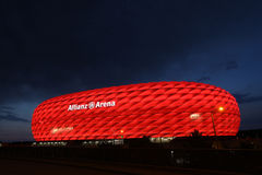 Red Allianz Arena. Famous landmark, exterior of the Allianz Arena in Munich, Germany. Night shot, the arena lit with red light, night sky as space for text, copy stock photography