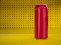 Red aluminum can on yellow and polka dot background. stock image
