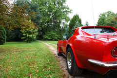 A red american car. A beautiful red Corvette on dirty road Royalty Free Stock Images
