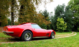A red american car with autumn colored trees. A red corvette standing on a dirty road in a park, with some autumn colored trees in the background Stock Images