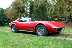 A red american car with autumn colors. A beautiful red Corvette with trees on autumn Royalty Free Stock Photos