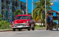 Red american classic car parked on the street in Varadero Cuba with a carriage Royalty Free Stock Photo