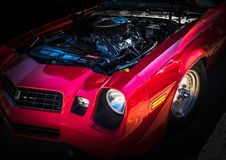 Red American Muscle Classc Car. Red american muscle classic car on black background with black grill and headlight and chrome rims Royalty Free Stock Image