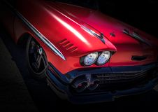 Red American Muscle Retro Car. Red american retro classic car on black background with black grill and headlight and chrome rims Royalty Free Stock Photos