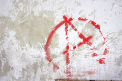 Red Anarchy Symbol Graffiti. A grunge scratched graffiti tag of the anarchy symbol on an old plaster wall in the town of Tarragona Spain Royalty Free Stock Photography