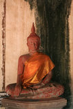 red ancient buddha statue in front of grunge wall Royalty Free Stock Photography