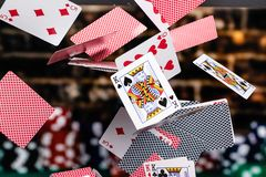Free Red And Blue Backed Playing Cards Cascading In Front Of A Background Of Stacked Poker Chips Stock Photos - 155531373