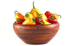 Red And Yellow Peppers In A Wood Bowl Stock Photography