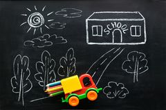 Free Red And Yellow Toy Car Carries Colorful Pencils To School House. Stock Images - 115355764