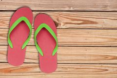 Red ang green flip flop sandals on wood Royalty Free Stock Photos