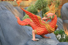 Red animal sculpture like chicken on the rock Royalty Free Stock Image