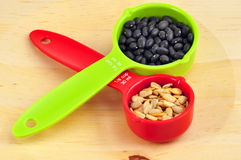 Red ans green measuring cups. On a diet: colorful measuring cups with black beans and sunflower seeds Royalty Free Stock Images