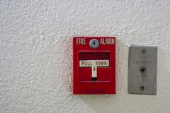 Red antique fire alarm button with white wall Stock Image