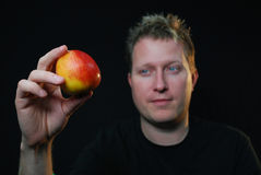 Red apple. Man holding red apple with black background Royalty Free Stock Images