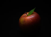 Red Apple. A red apple with green leaf partially obscured by the surrounding shadow stock photos