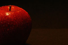 Red Apple. A red apple whith water drops on a black background Stock Image