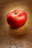 Red apple. On brown table Royalty Free Stock Image