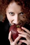 Red apple. Close-up of woman taking a bite of juicy fresh apple Royalty Free Stock Image