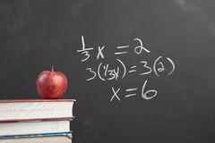 Red apple and algebra equation. An apple on stack of books by an algebra equation on the blackboard stock photography
