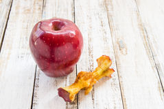 Red apple and apple core on a white wooden background Royalty Free Stock Photo