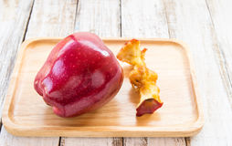Red apple and apple core in wooden plate on a white wooden backg Stock Photo