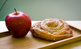 Red apple and baked roll stock photos