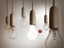 Red apple being thrown between light bulbs Royalty Free Stock Photo