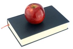 Red apple on black book Stock Photo