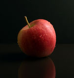 Red Apple on black reflective surface Stock Images