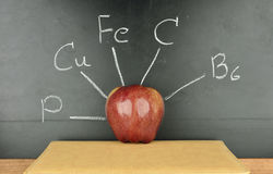 Red apple on blackboard. Red apple on a book and nutrient of apple writing on blackboard Stock Photo